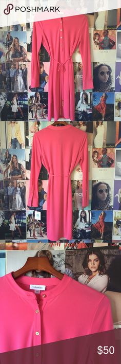 calvin klein + long sleeved dress This gorgeous coral jersey shirt/popover dress from Calvin Klein is super wearable and versatile. Gold buttons up the front and on the cuffs. Gold chain tassels on the ends of the ties. NWT. Calvin Klein Dresses Midi