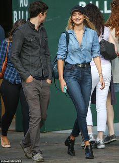 Shades of grey: The model looked happy to be on the trek with her male companion, who donned a dark denim jacket over jeans and a pair of loafers all in grey