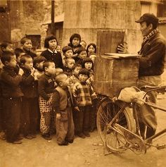 Boys being told a story in the street by a kamishibai story teller. This storytellers, would travel around with the kamishibai on the back of their bicycles, as they where relatively light and easy to transport. #kamishibai
