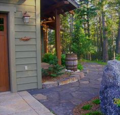 This front entryway is just gorgeous with a flagstone walkway wrapping around the corner past the rain barrel.