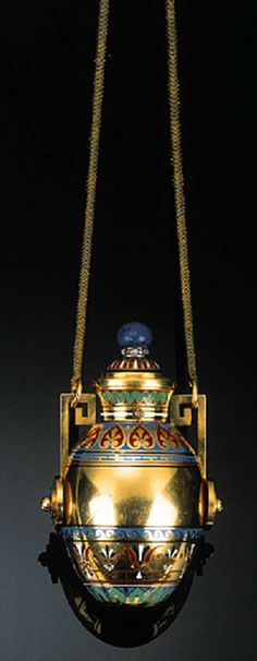 A MID 19TH CENTURY POLYCHROME ENAMEL, GOLD AND GEM-SET PERFUME BOTTLE  Modelled as an urn, the tapering ovoid yellow gold body decorated with concentric multi-coloured enamel designs, the domed hinged stopper with similar decoration and lapis lazuli bouton terminal above a band of rose-cut diamonds, the handles of a Greek key design, the whole suspended from a snake link chain, French control marks, 7 cm high