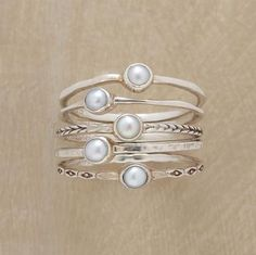 Pearl Ring Quintet Five cultured pearls are bezel set atop thread-thin silver bands, each different—polished, hammered and engraved. Handmade