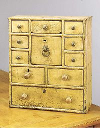 AN ENGLISH PAINTED CHEST/SPICE CABINET 19th century With an arrangement of eleven variously sized drawers with various handles, branded 'JWD' several times to the top surface 25in. (63cm.) high, 22in. (56cm.) wide, 10in. (25cm.) deep