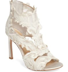 Pretty lace blossoms and swirls from the open toe to the zippered heel of this vintage-inspired sandal lifted skyward by a wrapped rectangular stiletto.