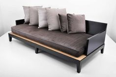 """Wonderfully designed, well crafted """"Opium"""" sofa/daybed with a dark stained, solid mahogany frame and woven raffia seat supporting a large upholstered seat cushion and six (6) large pillows. This elegant and comfortable sofa design retains its original Holly Hunt/Christian Liaigre metal tag.  dimensions: Height: 29.5, Width: 92.75, Depth: 44"""
