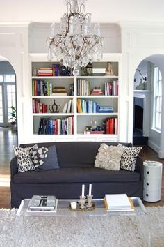 - Chic living room with white built-ins, navy blue slipcover sofa, ...