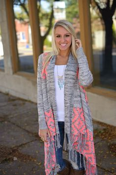 Long open cardigan with fringe asymmetrical hem and neon coral diamond print shoulders and back.