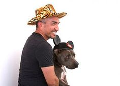 Cesar Millan posing in a photo booth with his dog Junior
