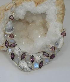 Artistic mix of polished cabachon Dendritic Opal gemstones in their natural organic colors, accented with marquis-cut and trillion-cut faceted amethyst gemstones and iridescent faceted Rainbow Moonsto