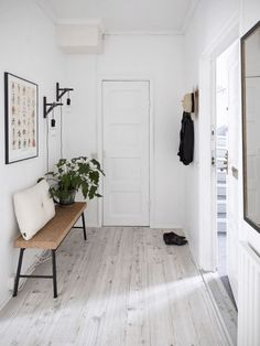 Clean and minimalist all-white entryway with iron accents and a pop of fresh greenery.