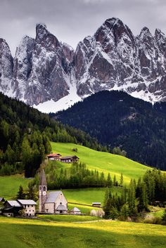 In the Shadow of Giants, A third view of the picturesque church of St. Magdalena in the Val di Funes, Italy. The hills are covered in yellow dandelions and those jagged peaks in the background are the Dolomites.