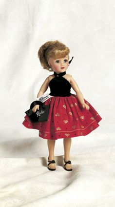 """Little Miss Revlon in Red and Black Cocktail Dress  With blonde ponytail,wearing girdle,petticoat,one- piece cocktail dress with black velvet top,red cotton skirt printed with gold fleur-de-lis design,black heels,black vinyl purse labeled """"Revlon"""",pearl earrings,in original box. Excellent condition. Z"""