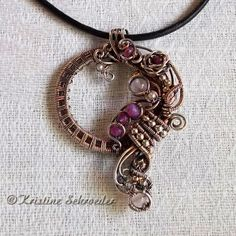 "©Kristine Schroeder, ""Memory's Mirror 2"", slide pendant in sterling silver, genuine ruby, rose quartz, garnet, cultured pearl. 2 inches by 1 1/4 inches. $350.00"
