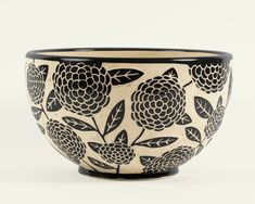 Gigantic Zinnia Bowl by Jennifer Falter. *Wheel thrown* *porcelain* bowl with a garden of flowers. The surface of this bowl is hand carved through a layer of black *slip* to create a contrasting and textural surface, using a technique known as *sgraffito*. Each piece is unique. Size and design may vary slightly from image shown. Signed on the bottom. Holds approx. 3 quarts.