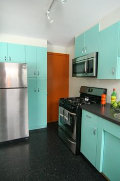 Kitchen with turquoise cabinets, black counter & black-speckled floor; white walls