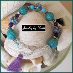 This trendy boho bracelet features gorgeous handmade polymer clay beads with a flower design in turquoise, purple, and green from Blue Morning Expressions. These hand painted beads dance among large t