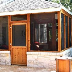 This screened porch is finished with natural looking stone and wood, complimenting the patio it opens up to.