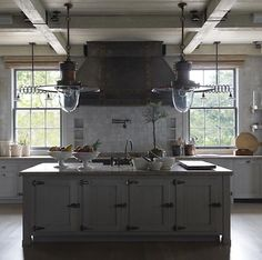 Grey Island with grey washed finished,,grey washed ceiling beams, no wall cabinetry, lots of windows, industrial looking glass and metal pendants