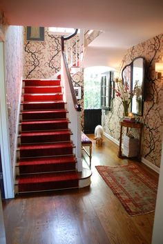 Entry..love the red stair runner, area rug, and wall paper.