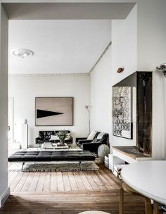 Nordic style living room with black mid century sofa, white walls, artwork and original wooden floor