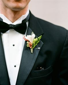 Incorporate Yuletide hues in an understated manner. This elegant boutonniere for a Christmastime wedding comprised white freesia, green seeded eucalyptus, and red pepperberry.