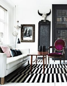 This monochrome living room is gorgeous! The beautiful plum velvet chair adds a welcome pop of colour and we can't get enough of that rug!