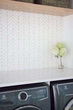 Modern laundry room remodel featuring herringbone wallpaper as a washable wallpaper backsplash.