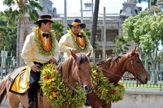 All decked out for the annual Kamehameha Day Parade in Honolulu. Two male pa'u (pah-uuh) riders and their mounts festooned in leis of orange ilima blossoms, the flower of the island of Oahu...they are riding past the only royal residence in the US, Iolani Palace...