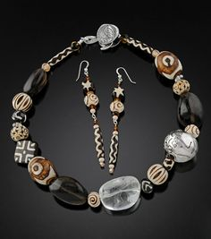 Designer: Joann Hendelman. Description: An incredible mix of bone, african mud beads, smokey quartz, burnt wood, Chinese painted wood, and batik bone and an original sculpted fine silver ball with FACE design. Because of the original sculpted REVERSIBLE sterling silver clasp the necklace can be worn in many ways.