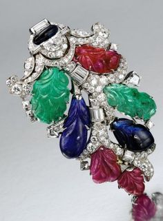 An Art Deco carved coloured stone and diamond clip, circa 1935. The shield-shaped cluster of foliate design decorated with carved emerald, ruby and sapphire leaves, on articulated stems set with numerous round and baguette diamonds, the terminal accented further with a half-moon-shaped diamond and a sapphire bead, mounted in platinum. #ArtDecp #clip
