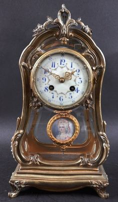 19TH CENTURY FRENCH ORMOLU MANTLE CLOCK with glass front and sides, the movement by G. & B., cream face, blue numbers and painted with garlands, the pendulum painted with a portrait of a pretty lady