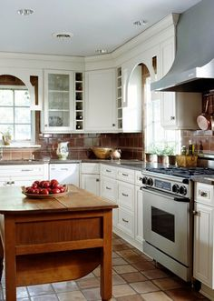 eclectic mix of American and Mediterranean styles, this sophisticated kitchen features decorative arches, a chocolate-brown tile backsplash, and Saltillo floor tiles. Brown balances the off-white cabinets. Arches add a touch of whimsy to the tradition Country White Kitchen, White Kitchen Island, Country Kitchen Designs, Country Kitchens, Small L Shaped Kitchens, L Shaped Kitchen Designs, Layout Design, Küchen Design, Design Ideas