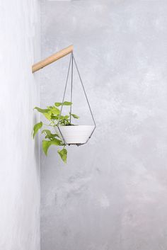 A hanging planter made with light grey cotton thread and a wood wall hook - perfect for hanging your favorite plants. The wood hook attaches