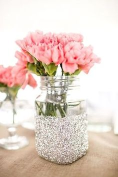 Glitter dipped mason jar with pink flowers. Perfect for a wedding shower centerpiece.