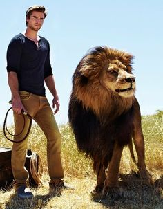 Liam Hemsworth. With a lion. now i'm kinda scared. i didn't know he was dangerous too!