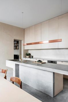 A kitchen with large poured concrete island bench that was cast directly on site. Contrasting the cool cement of the wall and floors are a rose-gold pendant light and neutral cabinetry Photography: Piet-Albert Goethals