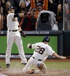San Francisco Giants' Marco Scutaro reacts as Buster Posey (28) scores during the third inning of Game 7 of baseball's National League championship series against the St. Louis Cardinals Monday, Oct. 22, 2012, in San Francisco.