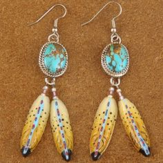 You'll love these Turquoise, Sterling Silver and dangling Feather earrings... they are the perfect start to a Native American jewelry collection! These handmade earrings are created in our shop in Gilbert, Arizona by Navajo, Verna Blackgoat. This lively pair features hand cut & hand polished cabochons of genuine Nevada Number Eight Turquoise. These lovely Turquoise stones are hand set in sawtooth Sterling Silver bezels and surrounded by hand twisted Sterling Silver wire rope. $66.00…