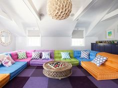 Check out this colorful modern game room with a wraparound sofa and purple checkered rug