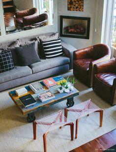 Sofá cinza com almofada p&b, poltronas de couro, mesa de centro de madeira de demolição e banquinhos de corda.