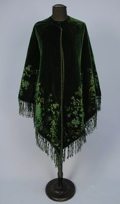 EMERALD GREEN CUT VELVET CAPE, 1870's - 1880's. Velvet triangle having a deep floral border with cord and velvet trim having knotted fringe and quilted silk lining