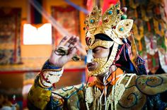 Tibetan Buddhist Monks in ceremonial clothes and ornaments perform the dance