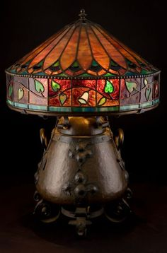 AN ONONDAGA COPPER AND IRON TABLE LAMP WITH LEADED GLASS SHADE Onondaga Metal Shops, Syracuse, New York, circa 1906 Engraved: OMS (interlaci...