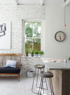 Rustic kitchen dining area with exposed brick wall