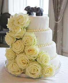 Bryllupskage i fire etager med friske hvide roser – perfekt til et sommerbryllup!