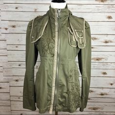"""[Diesel] Embroidered Military Jacket Parka Hooded Unique lightweight military style jacket by Diesel Clouds. Removable snap in hood with duck bill. Zip front. Skirted back with adjustable buckle at waist. Cool embroidery. Lined.  Color: Olive Green Fabric: 100% Cotton Bust: 17.5"""" Length: 25"""" Condition: GUC. Overall in excellent shape. Zipper pull is frayed. A snap is missing on the detachable hood in front. See last pic for details.  No Trades! Diesel Jackets & Coats Utility Jackets"""