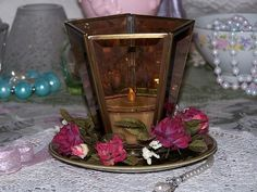 Brown glass chandelier cover, plate, strand of flowers, makes this candle holder.