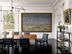 A 1920s light fixture by O.C. White Co. hangs above a George II mahogany table in the dining room, the chairs are custom made, and the console is from the 19th century; the 1897 seascape is by Paul Kuhstohs, and the portrait was found at a Paris flea market.   - ELLEDecor.com