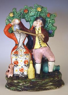19th Century Staffordshire pearlware figure group  forcing drink down her quite shocking