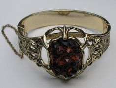 Bracelet with opening and chain holding large Amber chunk http://vintagecollector.ca/